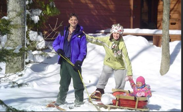 People snow shoeing with a child in a sled