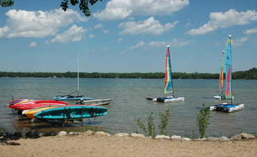 Boats and kayaks anchored on a lake